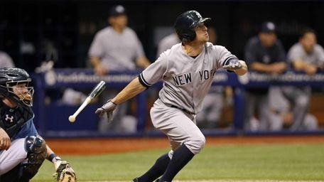 Yankees' Brett Gardner, right, follows through on a
