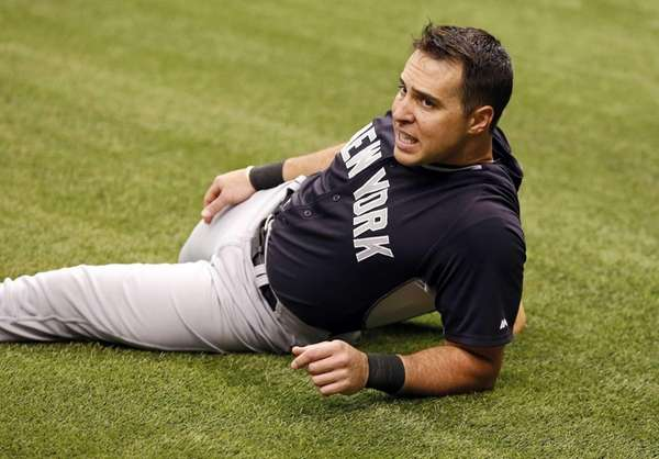 Yankees' Mark Teixeira stretches on the field for