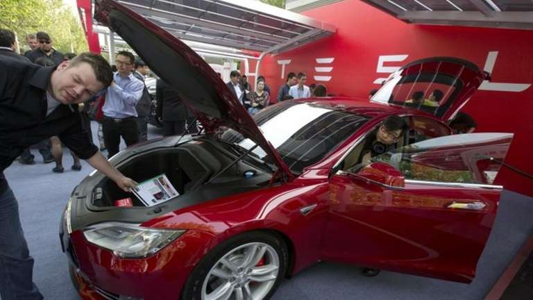Customers and journalists examine a Tesla Model S