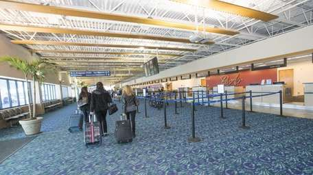Passengers look for their airline ticket counter inside