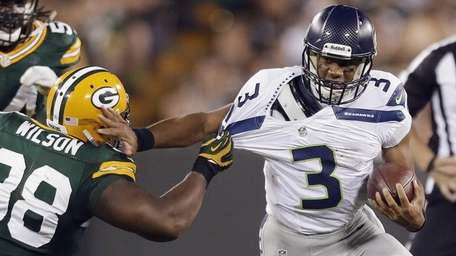 Seattle Seahawks quarterback Russell Wilson tries to get