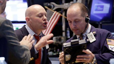 Traders Daniel Leporin, left, and Michael Urkonis work