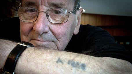 Holocaust survivor Werner Reich show his tatoo while