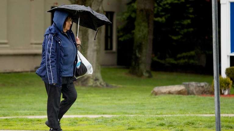 A woman walks with an umbrella in light