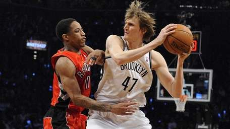 Andrei Kirilenko is defended by Raptors guard DeMar