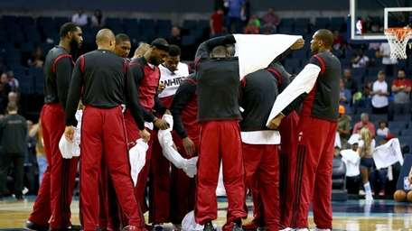 The Miami Heat huddle at center court as