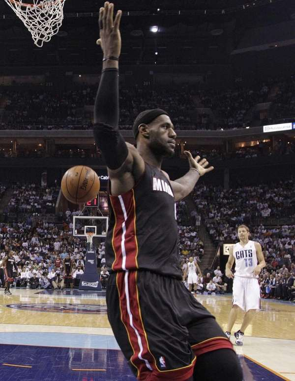Miami Heat's LeBron James gestures after dunking against