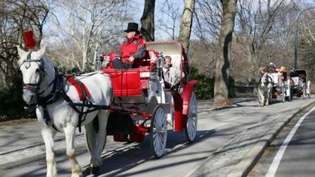 In this file photo, horse-drawn carriage roll through