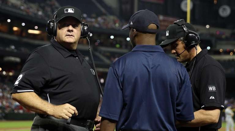 Umpires review a disputed call in a Mets