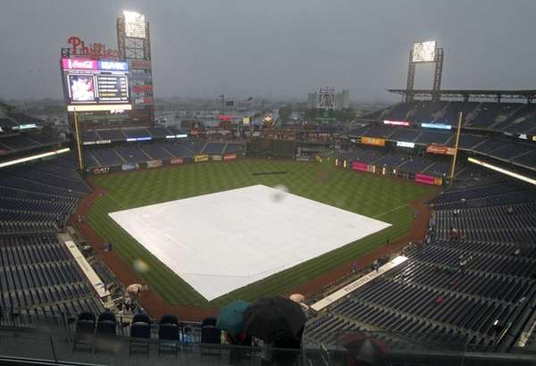 A tarp covers the infield as rain delays
