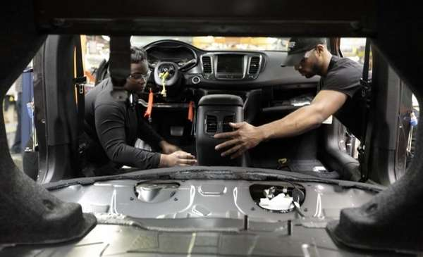 Assembly line workers build a 2015 Chrysler 200