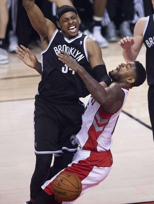 Toronto Raptors forward Amir Johnson, right, fouls Nets