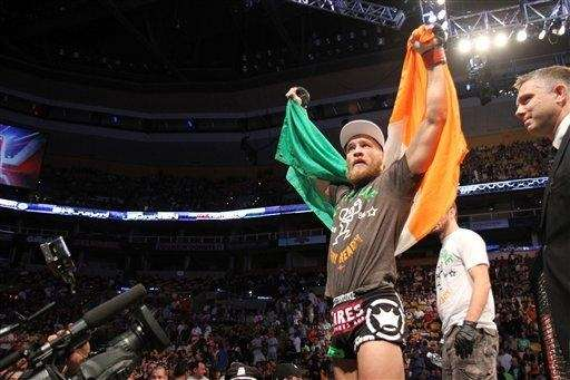 Conor McGregor, of Ireland, leaves the ring draped
