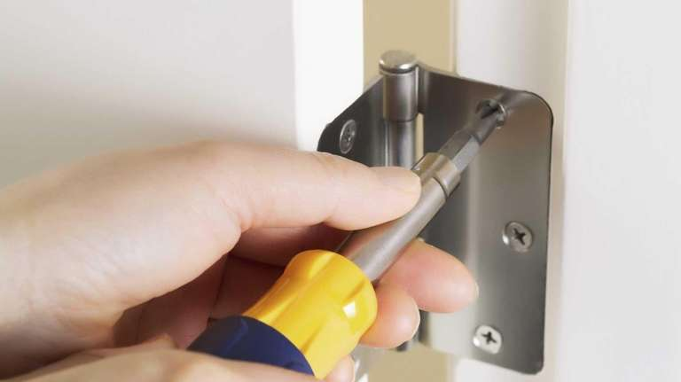 Photo of female hands, with screwdriver, tightening door