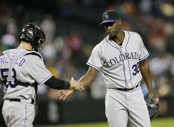 Colorado Rockies' LaTroy Hawkins, right, is congratulated by