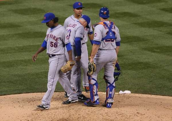Mets starting pitcher Jenrry Mejia, left, steps off