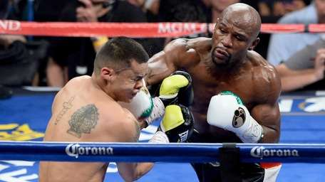 Floyd Mayweather Jr., right, throws a right at