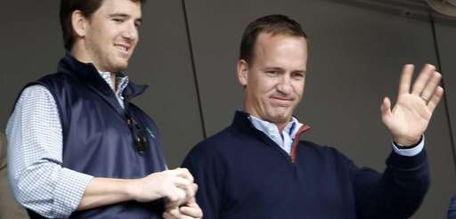 Denver Broncos quarterback Peyton Manning, right, waves to