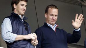 Denver Broncos quarterback Peyton Manning, right, waves to