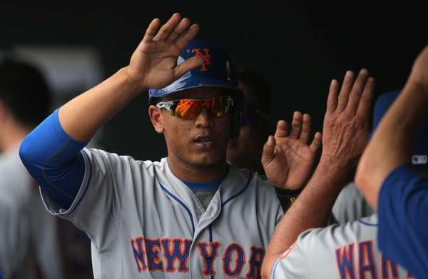 Juan Lagares celebrates in the dugout after scoring