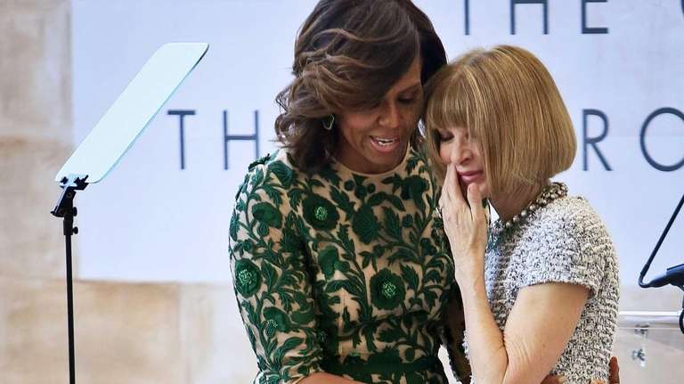 First lady Michelle Obama, left, embraces Vogue editor