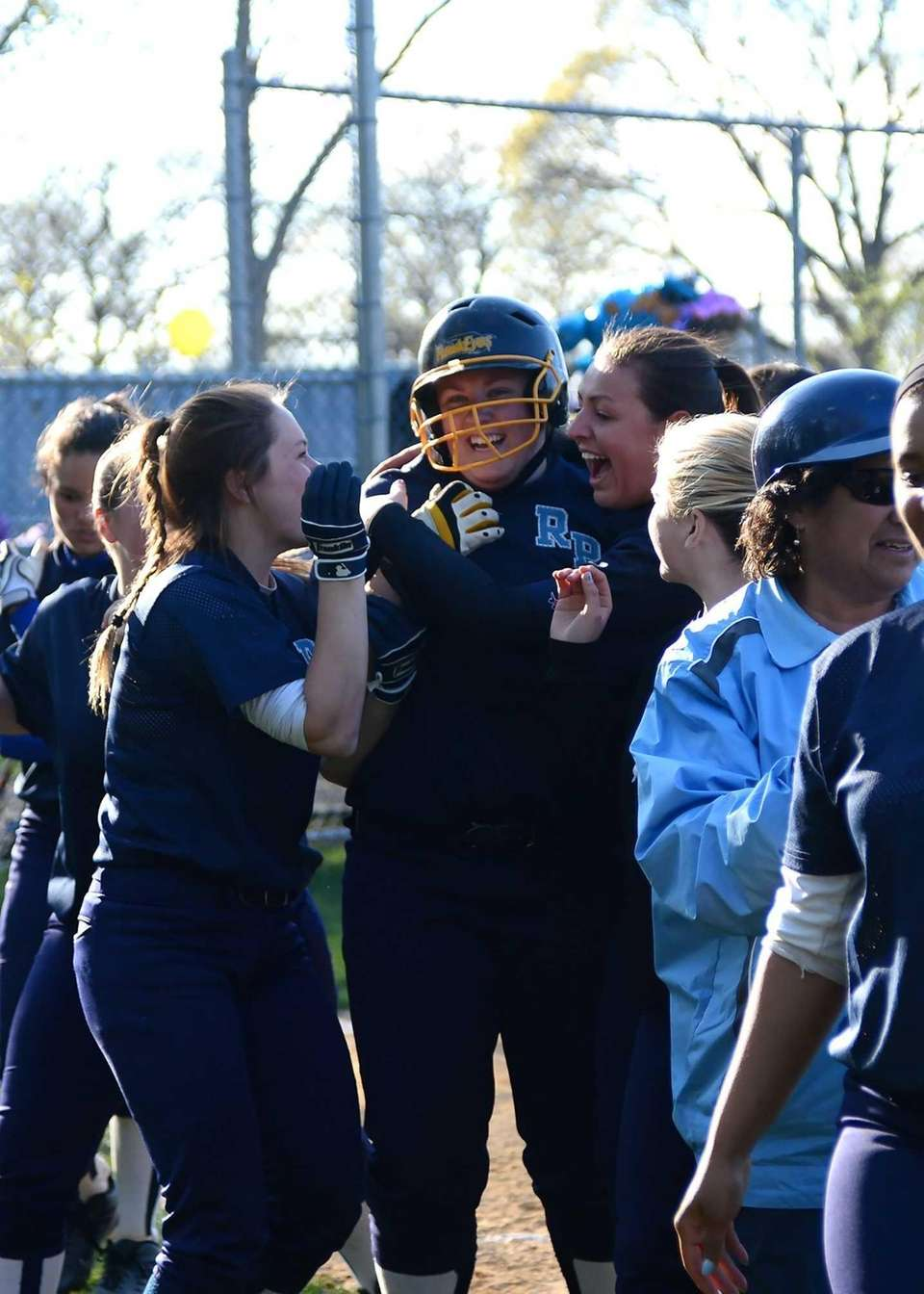 Rocky Point players congratulate Kelly Fitzpatrick, center, after