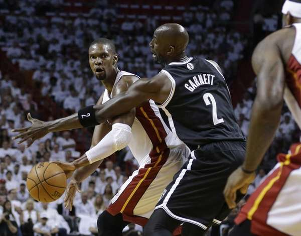 Miami Heat's Chris Bosh, left, passes as Nets'