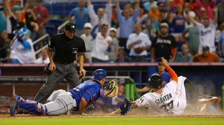 Giancarlo Stanton #27 of the Miami Marlins slides