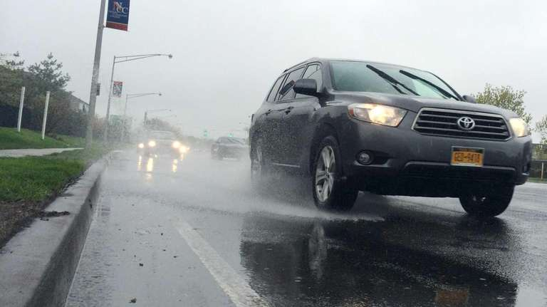 Cars drive along a rain-soaked Merchants Concourse in