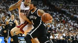 Deron Williams drives at the Miami Heat's Chris