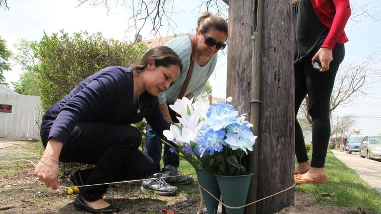 Women leave flowers at the scene of a