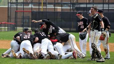 Patchogue-Medford players mob pitcher Andy Garcia after his