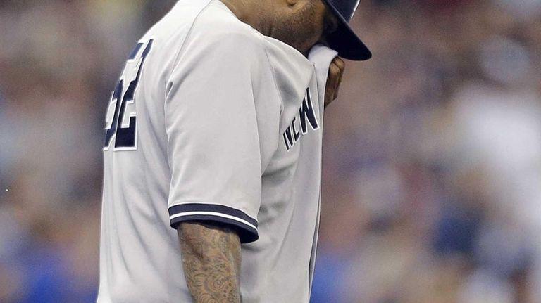 Yankees starting pitcher CC Sabathia wipes his face