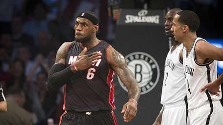 Miami Heat's LeBron James pounds his chest after