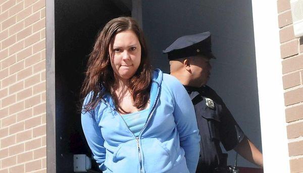 Sarah Knakal, 30, of Huntington Station, is led