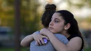 Kayla Olsen, 14, right, hugs a friend before