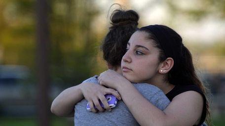 Kayla Olsen, 14, right, hugs a friend before