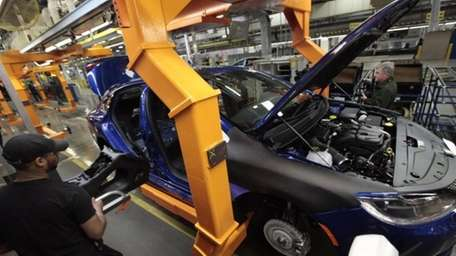 An assembly line worker builds a 2015 Chrysler