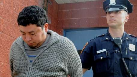 Elvis Espinal, 32, of Coram, is escorted from