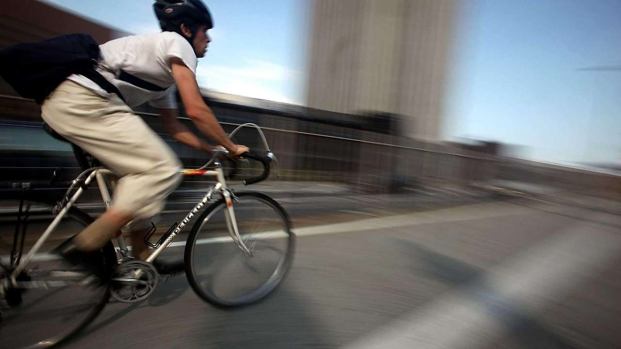 A cyclist crosses the Brooklyn Bridge during the