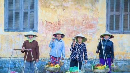 Women display their baskets of fruit in the