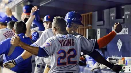 Mets outfielder Curtis Granderson celebrates in the dugout
