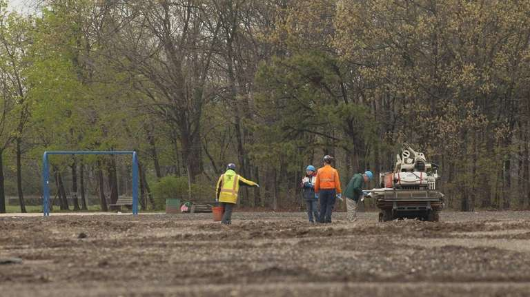 Workers are seen collecting soil samples at Roberto