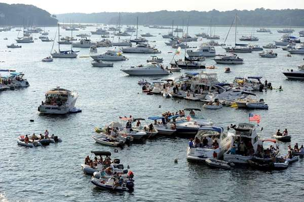 Festival-goers on boats listen to music at the
