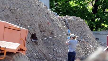 Investigators test dirt samples at a dumping site