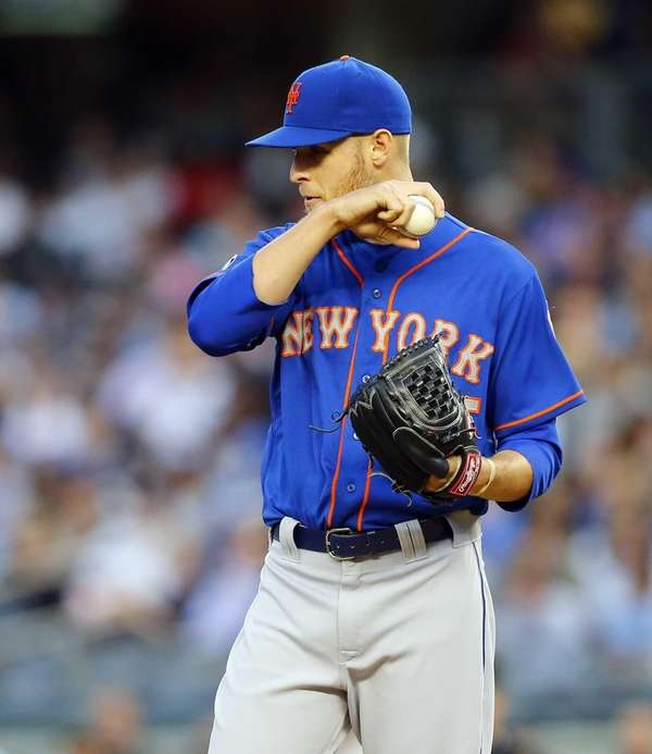 The Mets' Zack Wheeler wipes his face during