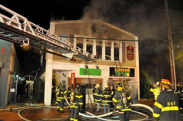 Firefighters battle an early morning fire on Main Street in Huntington Wednesday, May 14, 2014. No injuries were reported at the two-story commercial building that houses the Lemon Tree hair salon, the Osaka Sushi restaurant and second-floor office space, a Huntington Fire Department spokesman said.