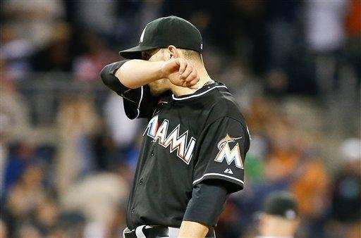 Miami Marlins starting pitcher Jose Fernandez wipes his