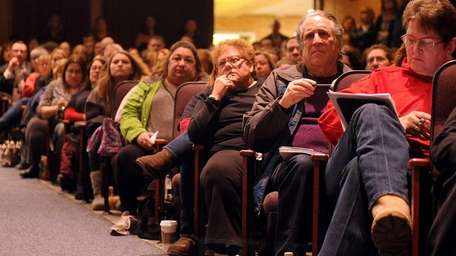 Audience members listen to a presentation regarding possible