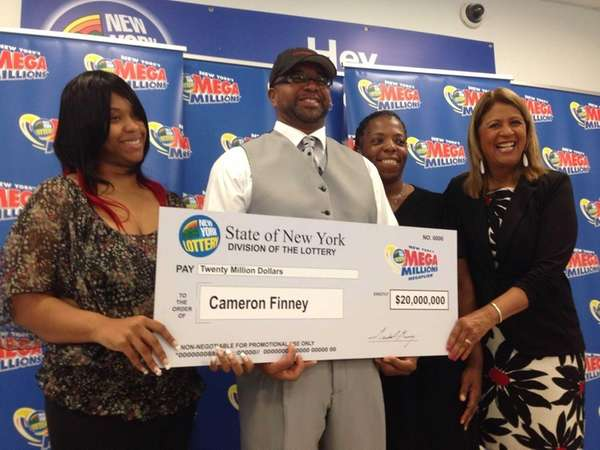 Cameron Finney, of Southampton, with daughter Christina, left, and wife Donna, join the New York State Lottery's Yolanda Vega at a ceremony on Thursday, May 15, 2014 in Plainview to announce the $20 million winner.